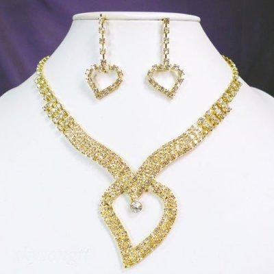 Parure de bijoux mariage ton or, cristal clair Ce délicat collier dont la pointe se termine par un coeur en cristal clair scintillant pour parfaire votre